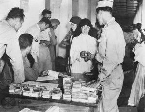 Sister Maria del Rey Danforth receiving American Red Cross supplies after being liberated from the Los Baños Internment Camp, Philippines, 1945