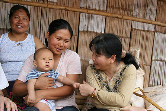 Tawny Thanh visiting with a mother and child, Thailand, 2005