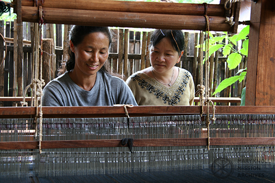 Tawny Thanh with refugee woman, weaving on a loom, Thailand, 2005