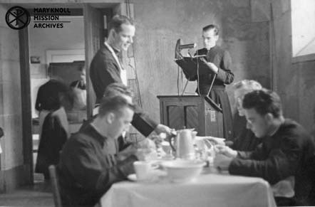 Seminarian reading a mission diary at mealtime in the Seminary Refectory, circa 1939